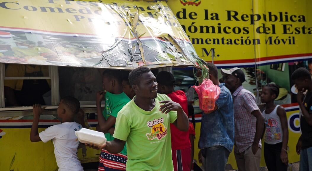 Un grupo de personas hace fila para reclamar alimentos, frente a un bus patrocinado por el Gobierno, en medio de la emergencia por el Covid-19, en Santo Domingo, República Dominicana, el 11 de mayo de 2020.