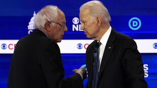 US Democratic presidential candidates Senator Bernie Sanders, left, and former Vice President Joe Biden talk at the 10th Democratic 2020 presidential debate at the Gaillard Center in Charleston, South Carolina.