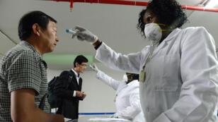 À l'aéroport de Nairobi, le 14 août, le personnel de santé prend la température des voyageurs