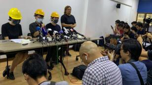 Trois manifestants masqués tiennent une conférence de presse à Hong Kong, le 6 août 2019.
