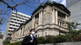 Un piéton marche devant le siège de la Banque du Japon à Tokyo le 16 mars 2020.