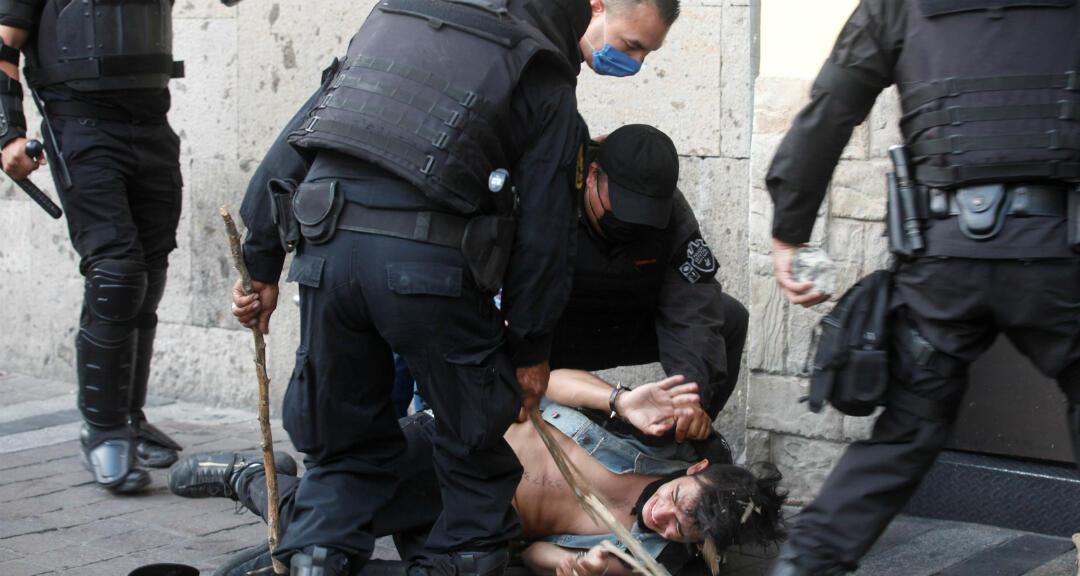 Policías detienen a un joven, afuera del Palacio de Gobierno de Jalisco, durante una protesta por la muerte de Giovanni López, golpeado por policías de Ixtlahuacan de los Membrillos en la ciudad de Guadalajara. 4 de junio de 2020.