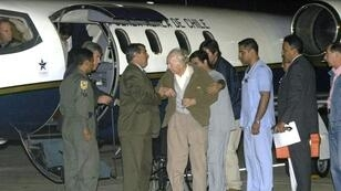 The sect's founder Paul Schaefer (centre), seen in March 2005, is helped aboard a Chilean Air Force Plane in Buenos Aires after being expelled from Argentina to Chile, where he died in jail