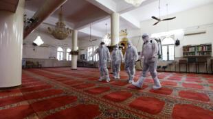 متطوعون فلسطينيون يرتدون ملابس واقية أثناء تطهير مسجد في القدس للمساعدة في مكافحة فيروس كورونا، 16 مارس/ آذار 2020