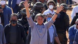 El presidente brasileño Jair Bolsonaro (C) saluda a seguidores en la inauguración de un hospital de campaña en Aguas Lindas, Brasil, el 5 de junio de 2020