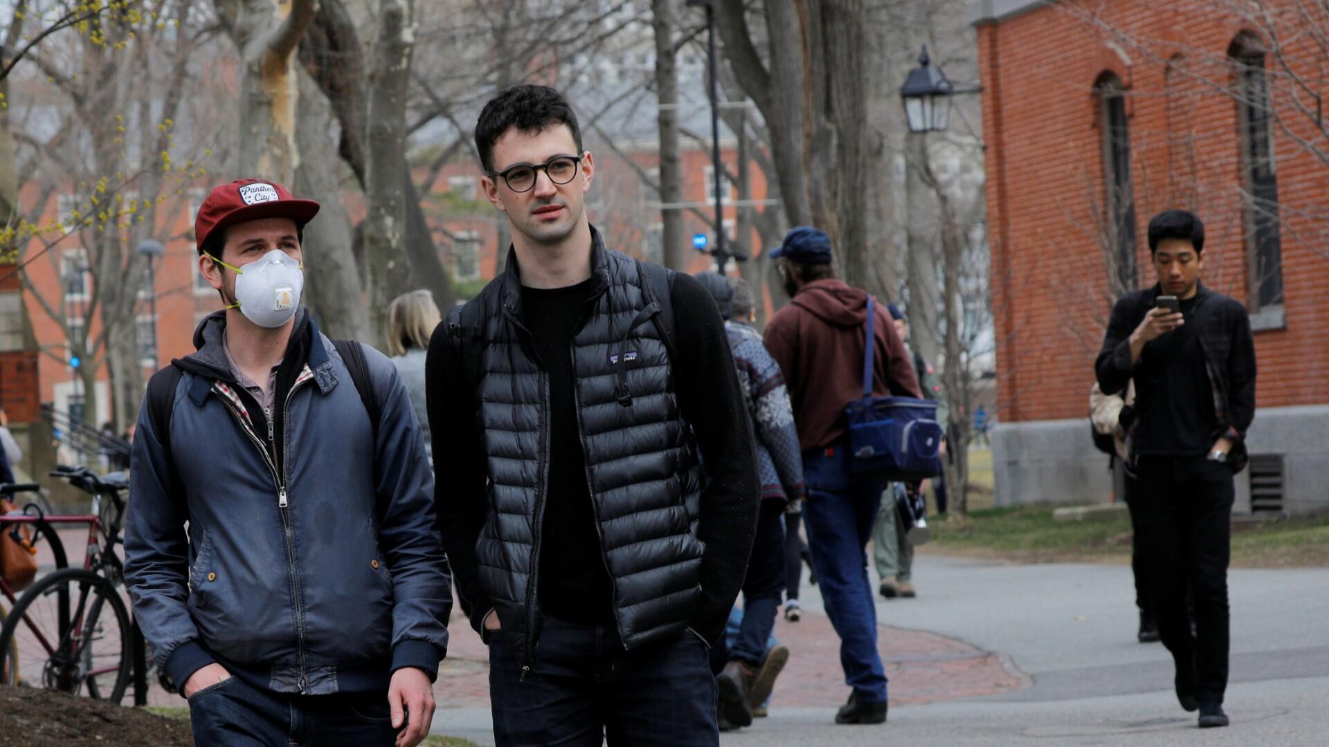 Un estudiante que usa una máscara, porque su tratamiento contra el cáncer lo ha dejado inmunodeprimido y vulnerable a enfermedades como el coronavirus, camina por el patio de la Universidad de Harvard, luego de que la escuela pidiera a sus estudiantes que no regresaran al campus después de las vacaciones de primavera