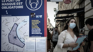 A woman wearing a protective mask walks past a sign showing the area where face coverings are mandatory in the city of Bordeaux, in southwestern France, on September 16, 2020.
