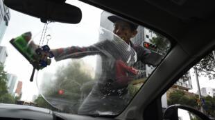 Un niño limpia el parabrisas de un automóvil en un semáforo en la avenida Reforma de Ciudad de México, el 25 de abril de 2020
