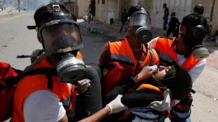 Palestinos buscan refugio ante el gas lacrimógeno en una multitudinaria protesta en la frontera entre Gaza e Israel. 14/5/18