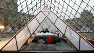 Trabajadores de Airbnb posan en la pirámide donde dormirán los ganadores del sorteo
