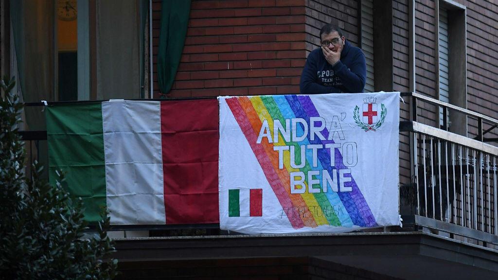 """Un hombre observa desde el balcón de un apartamento con una pancarta que dice """"Andrá Tutto Bene"""" - """"todo estará bien"""", una frase que se ha convertido en un símbolo de esperanza en la crisis del coronavirus en Italia, mientras el gobierno italiano continúa las medidas restrictivas de movimiento para combatir el brote de coronavirus, en Milán, Italia, el 14 de marzo de 2020."""