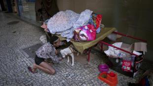 Una indigente juega con su perro en Rio de Janeiro, Brasil, el 23 de marzo de 2020