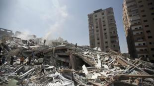 Des Palestiniens constatent les dégâts causés par la destruction d'un immeuble frappé par des tirs israéliens, en août 2014, dans la bande de Gaza.