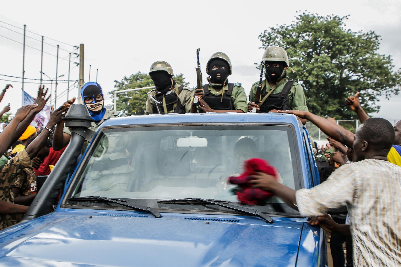 Des soldats maliens masqués arrivent sur la place de l'Indépendance, à Bamako, le 18 août 2020.
