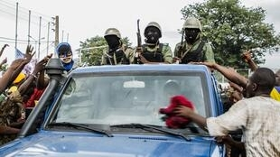 Masked soldiers arrive at Independence Plaza in Bamako, Mali on August 18, 2020.