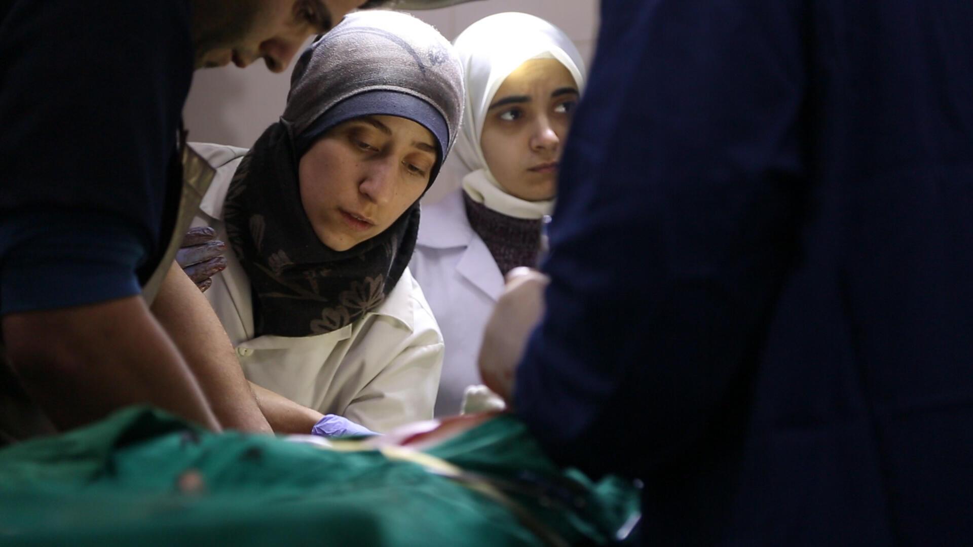 A la Ghouta, le Dr Amani (au centre) et le Dr Alaa en train d'opérer.