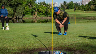 "Get in the hole: Jamiatul Akmal Abdul Jabar watches as she sinks a ""foot putt"" in Shah Alam, on the outskirts of Kuala Lumpur, during a round of ""footgolf"""
