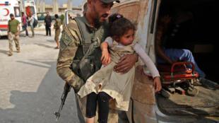 فتاة سورية يحملها مقاتل إلى سيارة الإسعاف لتلقي العلاج، في بلدة تل أبيض السورية، 20 أكتوبر/ تشرين الأول 2019.