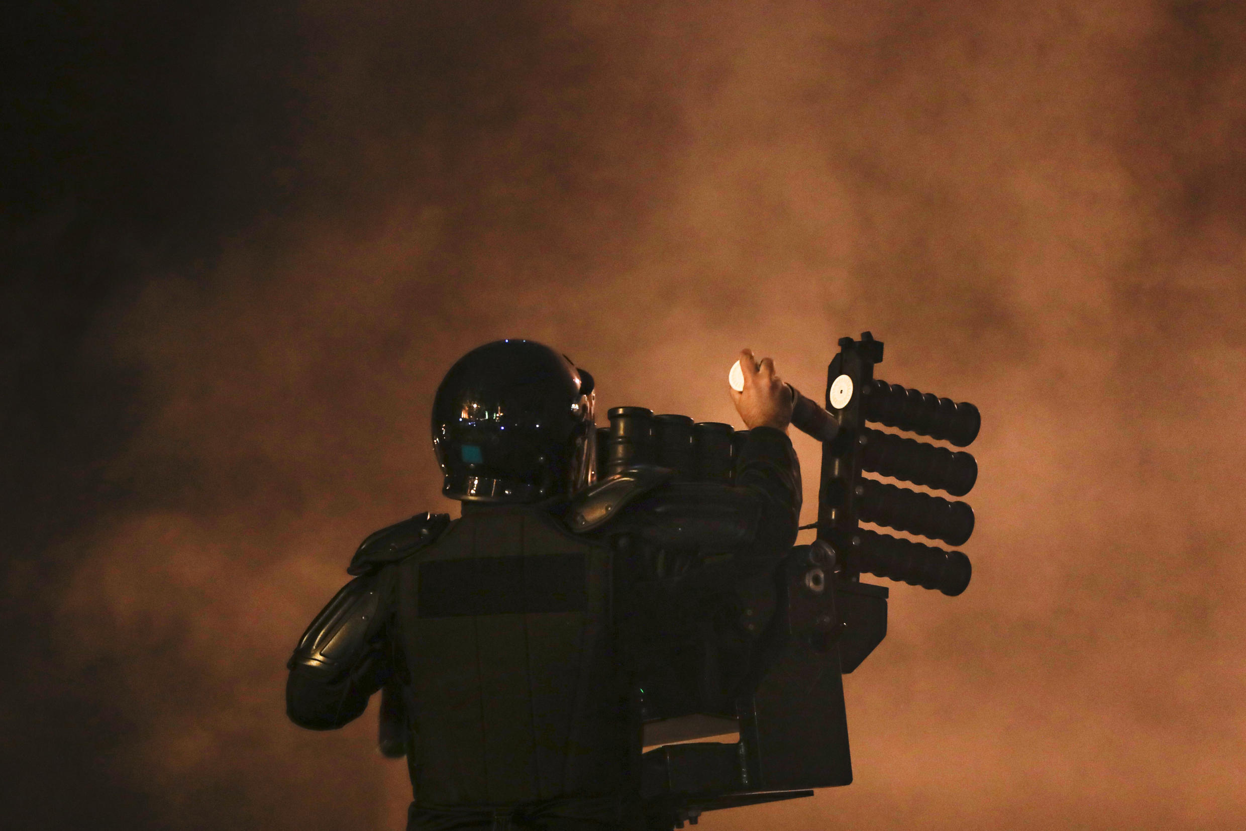Lebanese riot policeman loads tear gas canisters into a launcher during clashes with protesters Jan. 18, 2020.