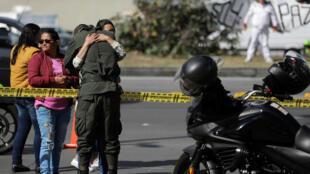 Una mujer abraza a un oficial de policía cerca de la escena donde un coche bomba explotó, según las autoridades, en Bogotá, Colombia, el 17 de enero de 2019.