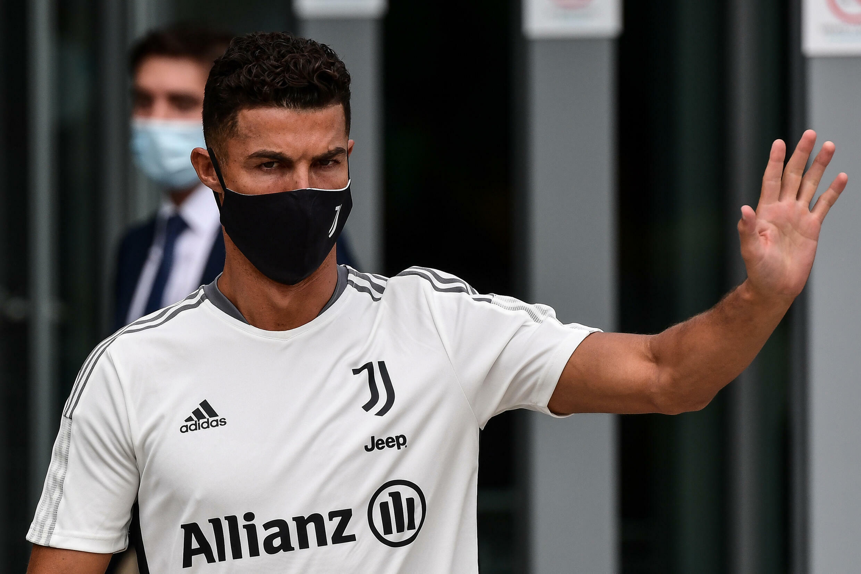 La estrella de la Juventus, Cristiano Ronaldo, saluda a los fanáticos después de su visita médica al centro médico del club el 26 de julio de 2021 en Turín.