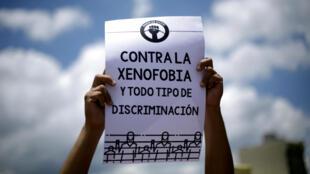 """Un hombre sostiene un letrero que dice """"Contra la xenofobia y todo tipo de discriminación"""", durante una marcha contra los actos de xenofobia y en solidaridad con los refugiados nicaragüenses, en San José, Costa Rica, el 25 de agosto de 2018."""