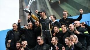 Le pilote français Jean-Eric Vergne en liesse (c) brandit le trophée après sa v victoire lors de l'étape de Paris du Championnat de Formule E, le 28 avril 2018