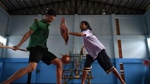 De jeunes thaïlandais pratiquent le Krabi Krabong le 8 juillet 2019 dans un gymnase de la banlieue de Bangkok