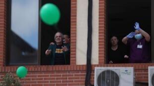 Los trabajadores y residentes de hogares de ancianos miran globos después de su liberación en el aire como un tributo a los residentes que fallecieron y celebran que haber permanecido libres de la enfermedad por coronavirus durante más de dos semanas en el Centro Casaverde en Navalcarnero, fuera de Madrid, España, 13 de mayo de 2020.