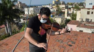 El violinista cubano William Roblejo ensaya en el techo de su casa en La Habana, el 15 de abril de 2020