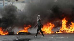 Un manifestante pasa junto a una barricada en llamas durante protestas antigubernamentales en Puerto Príncipe, Haití, el 15 de febrero de 2019.