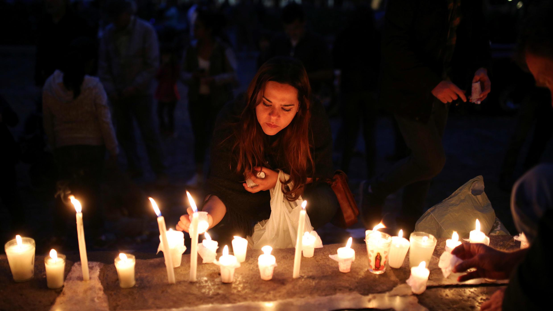 Una mujer enciende una vela en memoria a las víctimas de la erupción del volcán de Fuego en Antigua, Guatemala, el 9 de junio de 2018.