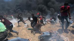 Manifestantes palestinos huyen del fuego israelí y del gas lacrimógeno durante una protesta contra la embajada de Estados Unidos en Jerusalén y antes del 70 aniversario de Nakba, en la frontera entre Israel y Gaza en el sur de la Franja de Gaza el 14 de mayo de 2018.