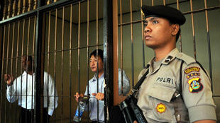 An Indonesian policeman stands guard next to a detention room where Australians Myuran Sukumaran (L) and Andrew Chan wait for their trial on drug charges in Denpasar on the island of Bali on October 8, 2010.