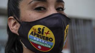 """Une femme porte un masque sur lequel on peut lire """"J'approuve"""" avant le référendum constitutionnel du 25 octobre, à Santiago du Chili, le 22 septembre 2020"""