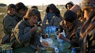"""Yezidi boys share a meal in Syrian Democratic Forces-held territory after escaping the last scrap of the Islamic State group's collapsed """"caliphate"""""""