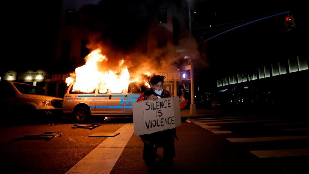 """Un manifestante sositene un cartel que indica """"el silencio es violencia"""" frente a un coche de policía ardiendo en Nueva York, Estados Unidos, durante las protestas del sábado 30 de mayo de 2020 contra la muerte del afroamericano George Floyd bajo custodia policial."""