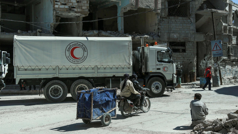 Camiones de la Media Luna Roja transportan ayuda humanitaria como parte de un convoy del Comité Internacional de la Cruz Roja (CICR) y la ONU en la ciudad de Duma, en el enclave de Guta Oriental, el 9 de marzo de 2018.