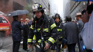 Bomberos hacen presencia en la 787 - 7th Avenida en el centro de Manhattan, donde se informó que un helicóptero se estrelló en la ciudad de Nueva York, EE. UU., el 10 de junio de 2019.
