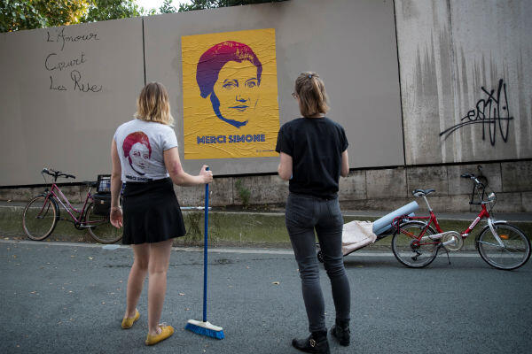 "Street artists from the collective ""Merci Simone"" set up a poster in Paris, on June 28, 2018."