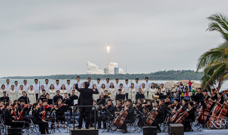 Una banda toca música mientras un cohete Long March 5B, que transporta el módulo central de la estación espacial Tianhe de China, despega del Centro de Lanzamiento Espacial de Wenchang, en la provincia de Hainan, el 29 de abril de 2021