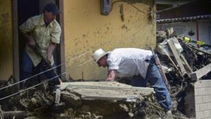 Des hommes essayent de nettoyer leur habitation dans la ville de Salgar en Colombie, le 18 mai 2015