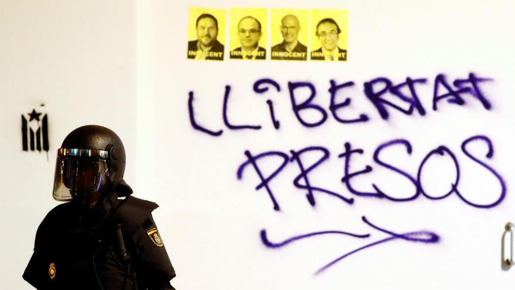 """Un policía antidisturbios se para frente a una pared con fotos de los políticos encarcelados por el 'procés' y una pintada que dice """"libertad para los presos políticos"""". Barcelona, España, el 18 de octubre de 2019."""