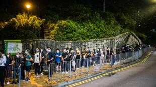 ناشطون مؤيدون للديموقراطية في هونغ كونغ يصطفون في 15 حزيران/يونيو 2020 لاحياء الذكرى الاولى لرحيل رجل توفي اثناء قيامه بتعليق لافتة احتجاج.