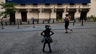 Des passants déambulent devant le New York Stock Exchange (NYSE) à Wall Street (New York), le 13 juillet 2020