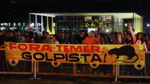 """Des manifestants brandissant une pancarte """"Termer dehors"""" devant le palais présidentiel à Brasilia, le 17 mai 2017."""