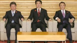 El primer ministro japonés, Shinzo Abe (centro), entre su ministro de Finanzas, Taro Aso (dcha), y el de Economía, Comercio e Industria, Toshimitsu Motegi, en una reunión extraordinaria del gabinete de gobierno en Tokio, este 15 de octubre de 2018