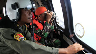 Indonesian crew members observe the surface of the sea during the search for AirAsia flight QZ8501 on board an aircraft over The Java Sea on January 1, 2015