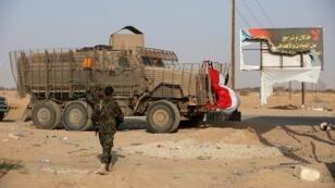 جندي من القوات الحكومية اليمنية يمر إلى جانب آلية عسكرية تابعة للانفصاليين الجنوبيين في محافظة شبوة. 27 أغسطس/آب