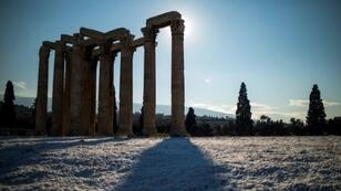 The ancient Temple of Zeus towers over an unusual blanketing of snow on Athens' Acropolis